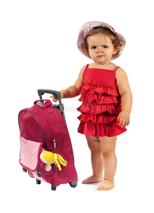 Niña lista para viajar - colocándose al lado de un equipaje rojo fotografía de archivo