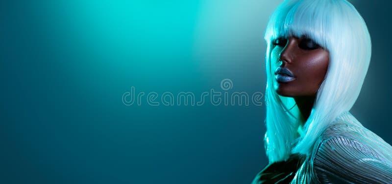 Niña modelo de alta moda con coloridas luces de neón brillantes posando en el estudio, retrato de una hermosa mujer afroamerican foto de archivo