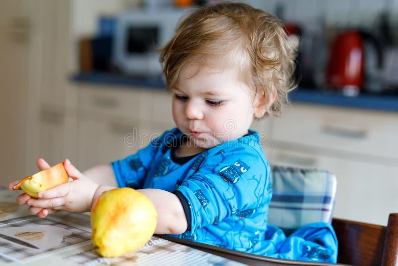 Niña pequeña adorable linda que come la pera fresca Niño feliz hambriento del bebé de un año que sostiene la fruta foto de archivo