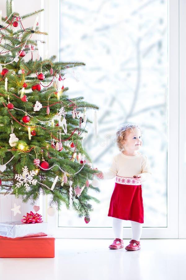 Niña pequeña adorable que adorna un árbol de navidad hermoso imagen de archivo
