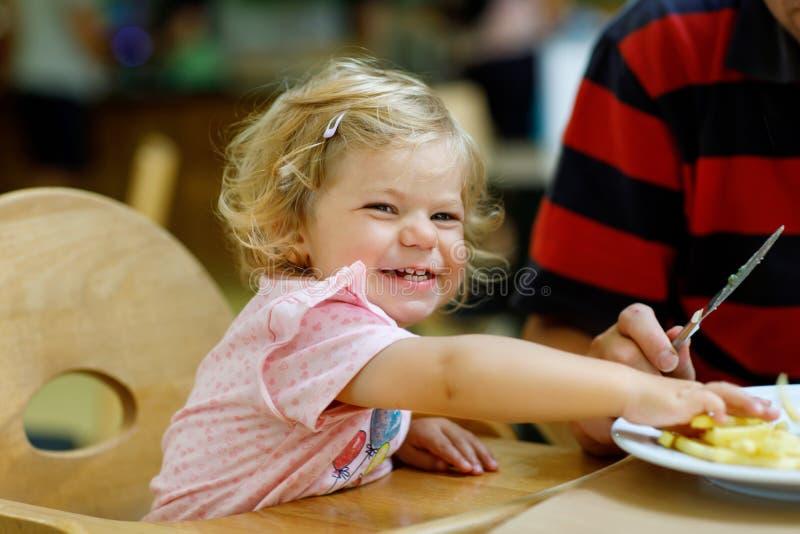 Niña pequeña adorable que come verduras sanas y papases fritas malsanos Niño feliz lindo del bebé que toma la comida foto de archivo