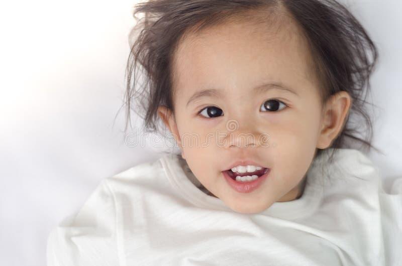 Niña pequeña asiática que miente en la cama en casa fotos de archivo libres de regalías