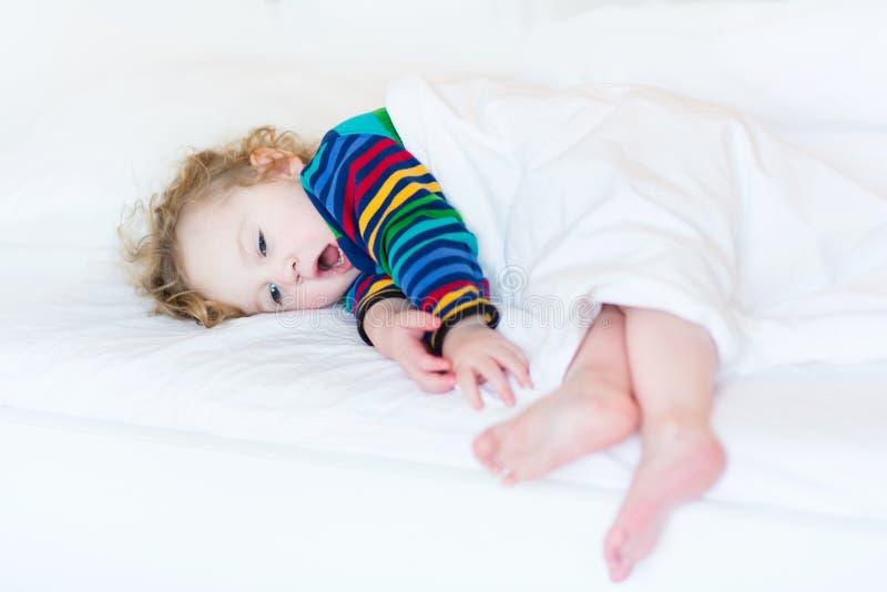 Niña pequeña de bostezo divertida que toma siesta en la cama blanca fotografía de archivo libre de regalías