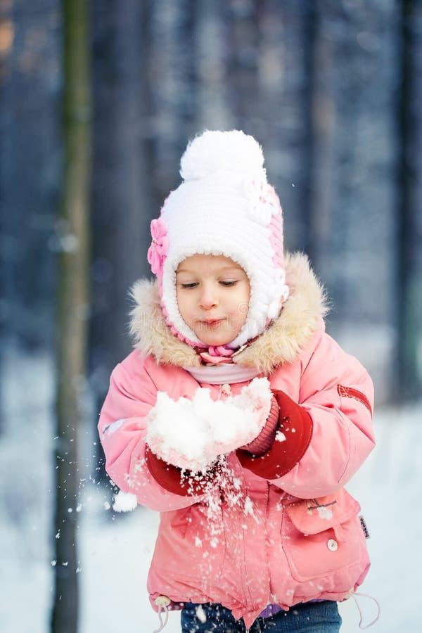 Niña pequeña de risa feliz en un bosque nevoso hermoso del invierno foto de archivo