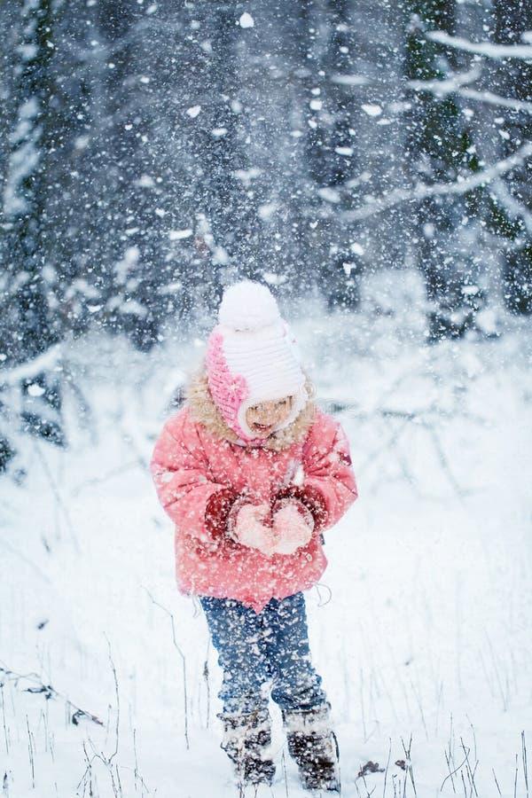 Niña pequeña de risa feliz en un bosque nevoso hermoso del invierno imagen de archivo libre de regalías