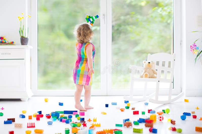 Niña pequeña de risa linda que juega con los bloques coloridos imagen de archivo libre de regalías