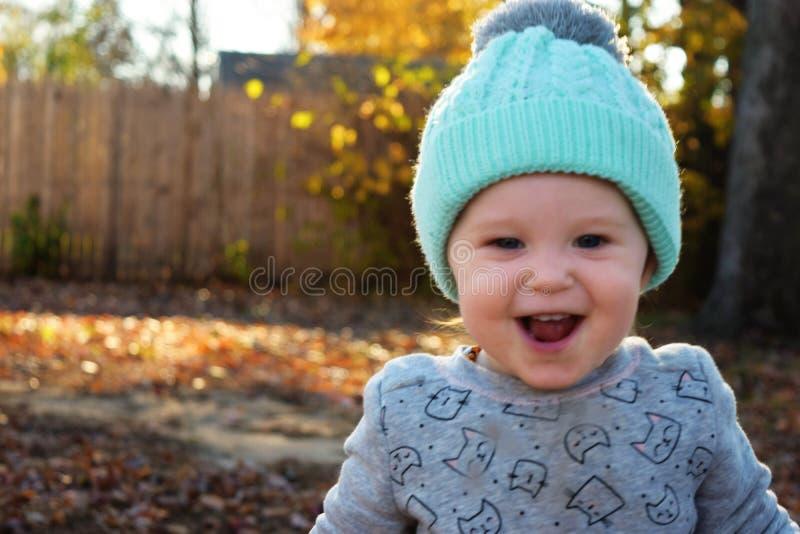 Niña pequeña emocionada que juega en hojas fotos de archivo