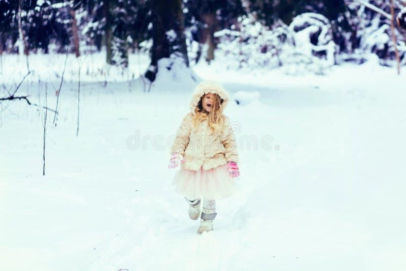 Niña pequeña en abrigo de pieles que camina en un parque nevoso del invierno fotos de archivo libres de regalías