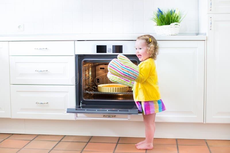 Niña pequeña en manoplas de la cocina al lado del horno con la empanada de manzana foto de archivo libre de regalías