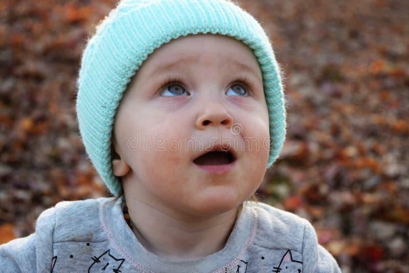 Niña pequeña en sombrero azul que mira fijamente el cielo imágenes de archivo libres de regalías