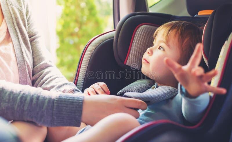 Niña pequeña en su asiento de carro imagenes de archivo