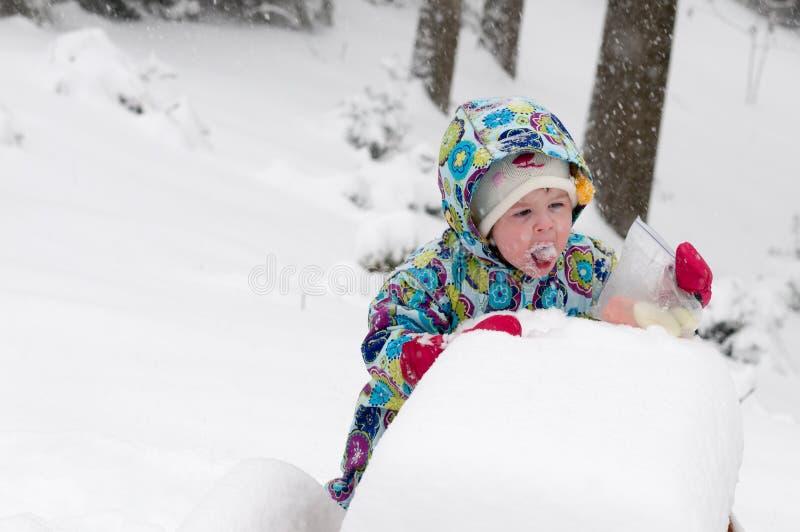 Niña pequeña feliz en capa caliente y sombrero hecho punto que lanza encima de nieve y que se divierte en el invierno afuera, ret imágenes de archivo libres de regalías