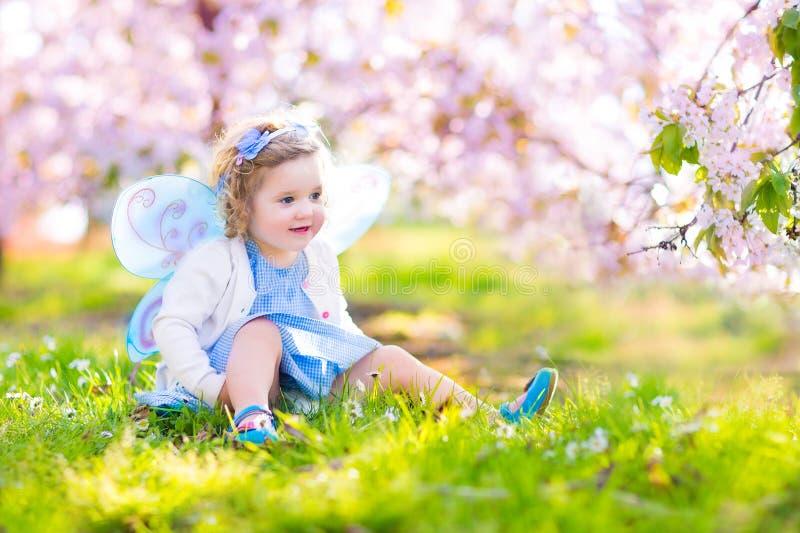 Niña pequeña hermosa en traje de hadas en jardín de la fruta foto de archivo libre de regalías