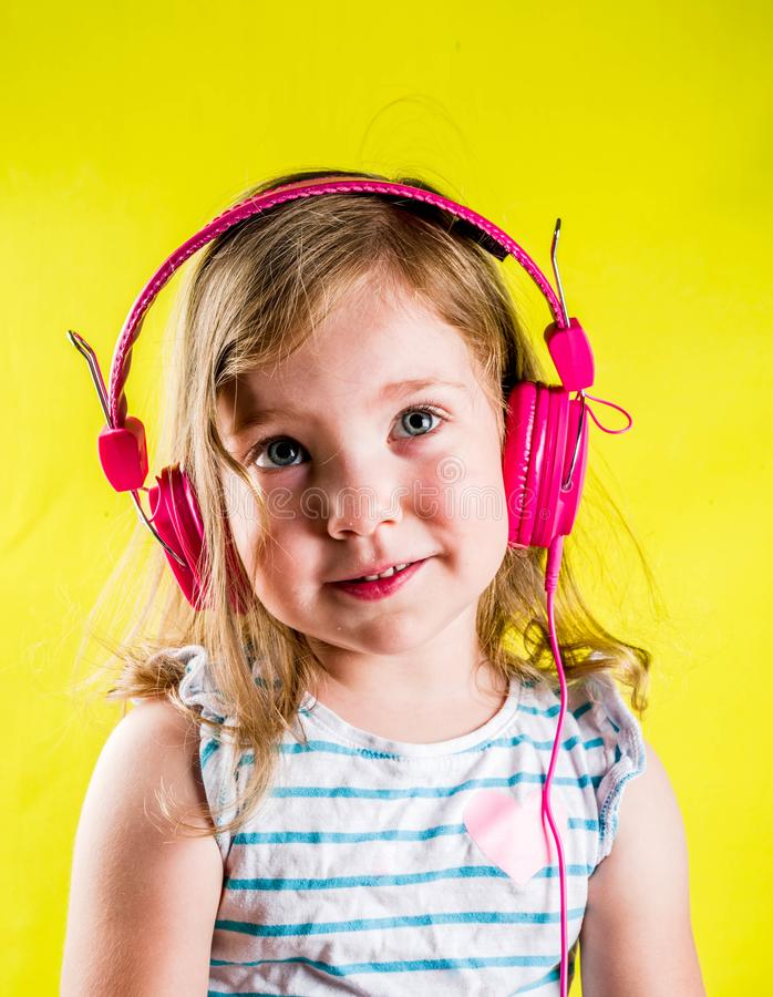 Niña pequeña linda con los auriculares imágenes de archivo libres de regalías
