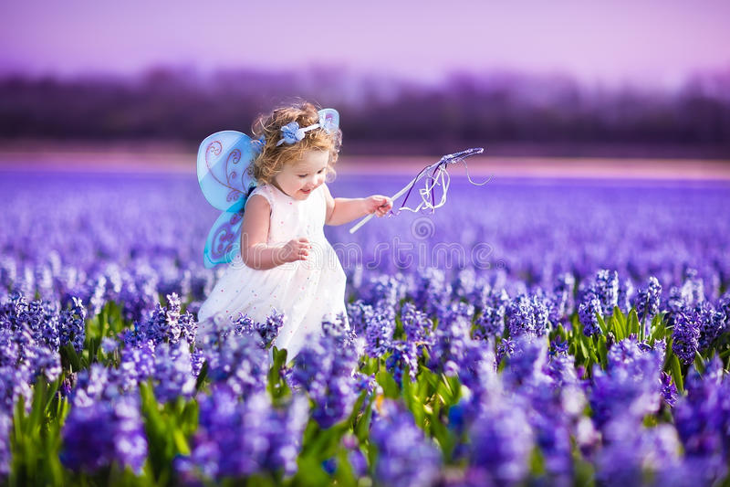Niña pequeña linda en traje de hadas en un campo de flor foto de archivo libre de regalías