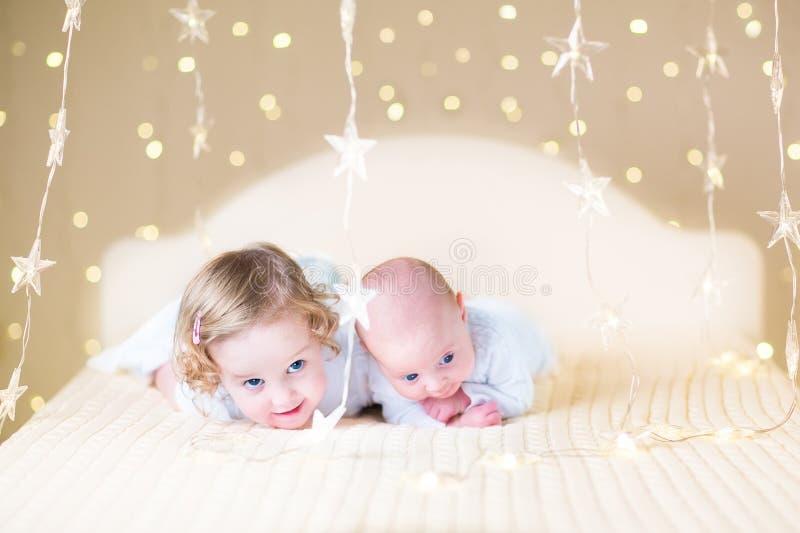 Niña pequeña linda y su pequeño hermano recién nacido del bebé con las luces suaves calientes imagenes de archivo