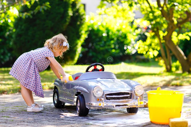 Niña pequeña magnífica linda que lava el coche viejo grande del juguete en jardín del verano, al aire libre Coche sano feliz de l fotografía de archivo libre de regalías