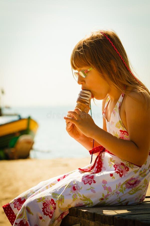 Niña pequeña que come el helado en la playa fotografía de archivo libre de regalías