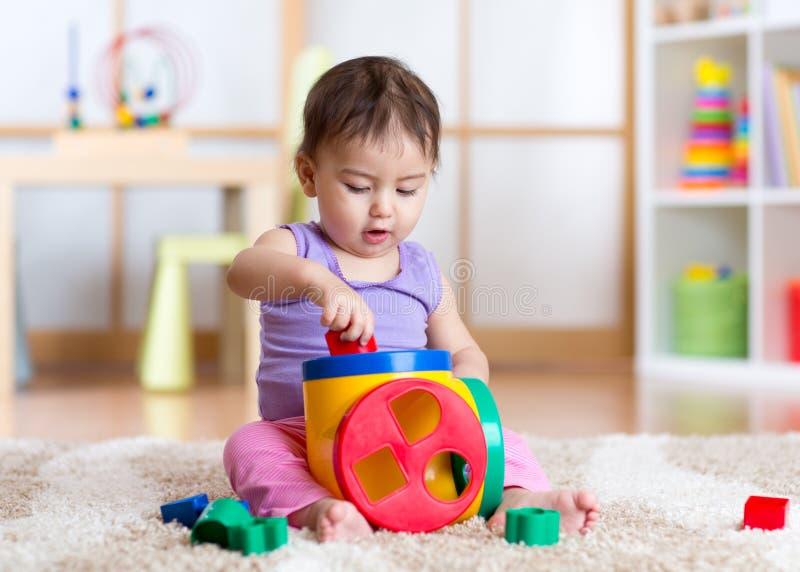 Niña pequeña que juega dentro con el juguete del clasificador que se sienta en la alfombra suave foto de archivo