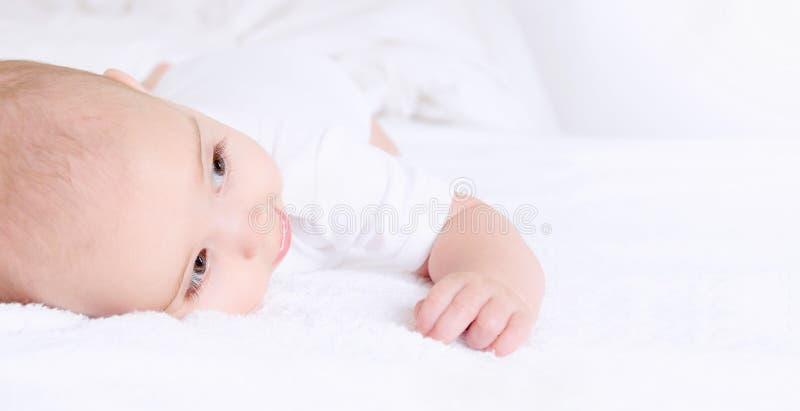 Niña pequeña que miente y que sonríe feliz en la manta imágenes de archivo libres de regalías