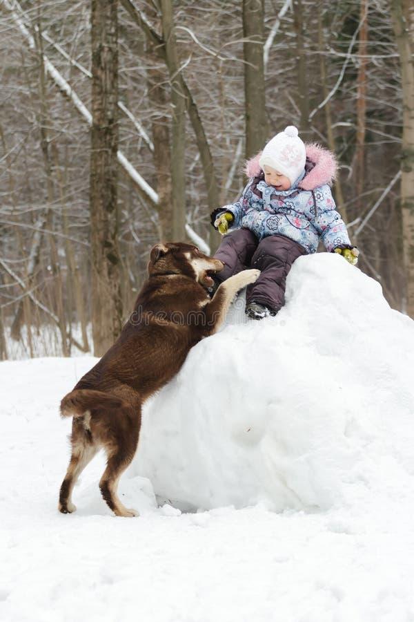 Niña pequeña que se divierte el invierno en la colina nevosa con fotografía de archivo