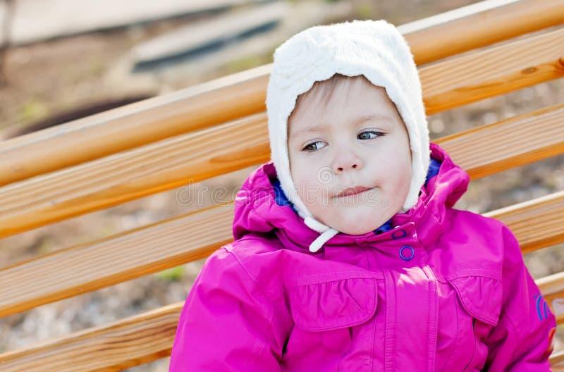 Niña pequeña que se sienta en el banco imágenes de archivo libres de regalías