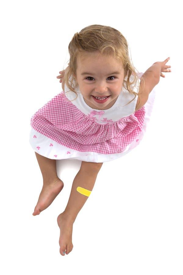 Niña pequeña que sonríe en su vestido rosado imagen de archivo