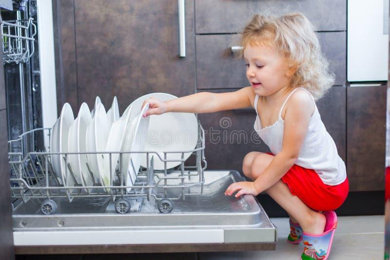 Niña pequeña rubia linda que ayuda en la cocina que saca las placas de la lavadora del plato imagen de archivo libre de regalías