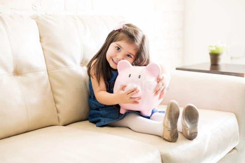 Niña preciosa con su hucha en casa fotos de archivo libres de regalías