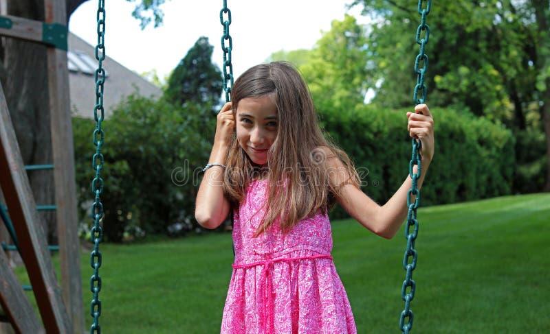 Niña preciosa en los oscilaciones en el parque con el vestido rosado durante verano en Michigan fotografía de archivo