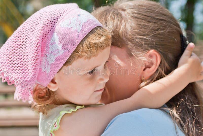 Niña que abraza el cuello de su madre, sonriendo fotografía de archivo libre de regalías