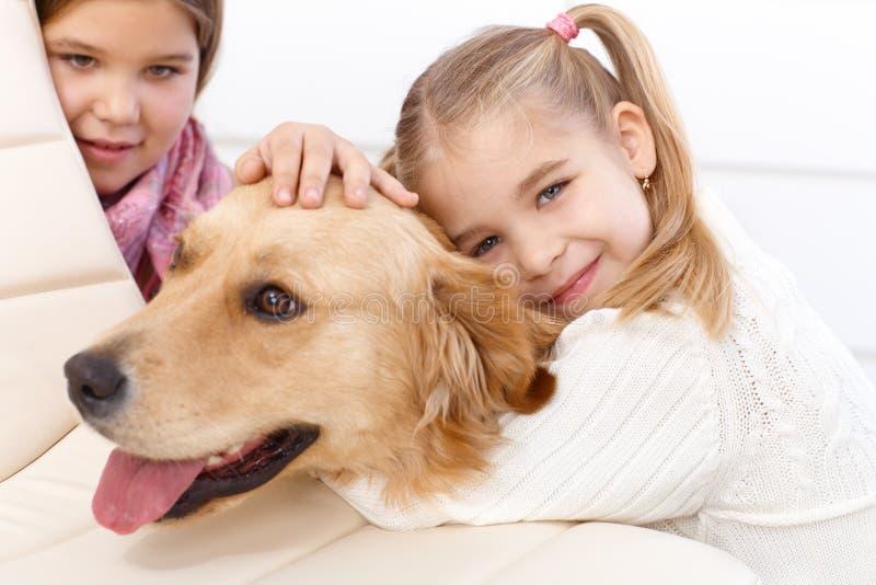 Niña que abraza la sonrisa del perro de animal doméstico imagenes de archivo