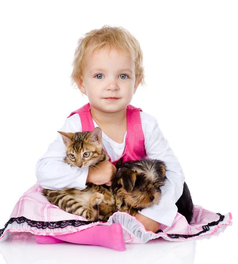 Niña que abraza un gatito y un perrito Aislado en blanco fotos de archivo