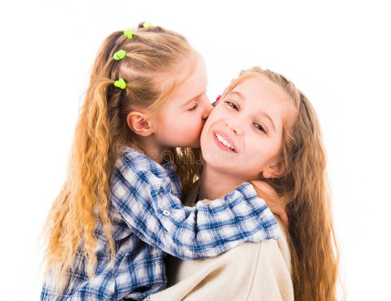 Niña que abraza y que besa a su más vieja hermana fotos de archivo