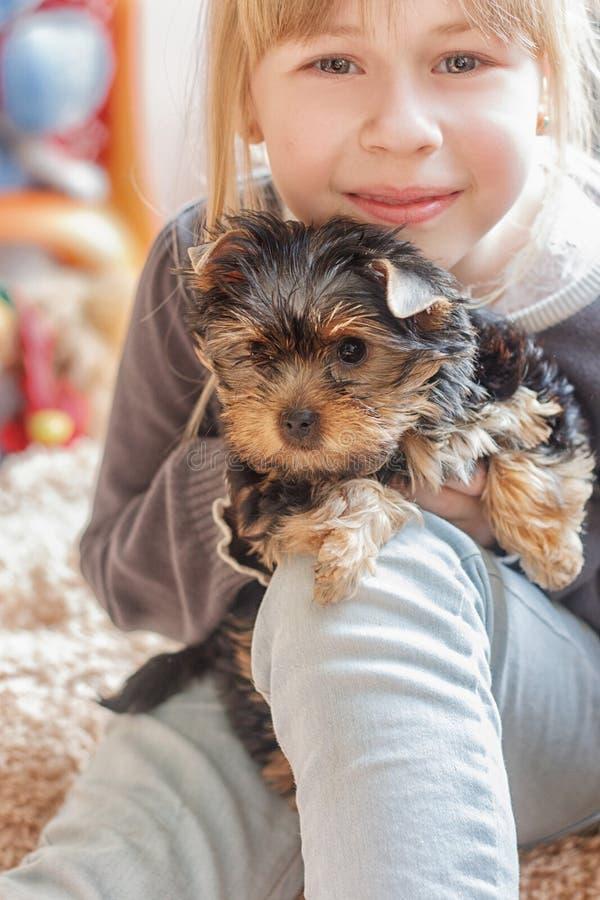 Niña que abraza Yorkshire Terrier imágenes de archivo libres de regalías