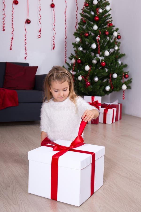 Niña que abre la caja de regalo grande cerca del árbol de navidad en casa imagenes de archivo