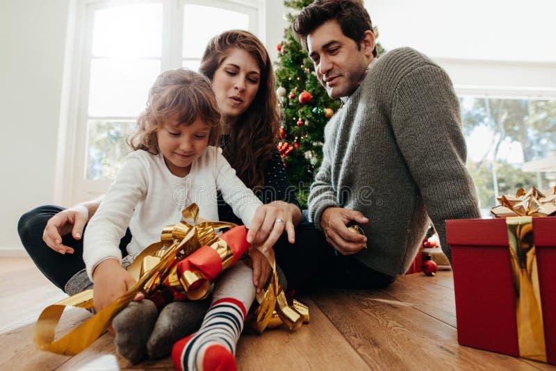Niña que abre sus regalos de la Navidad foto de archivo libre de regalías