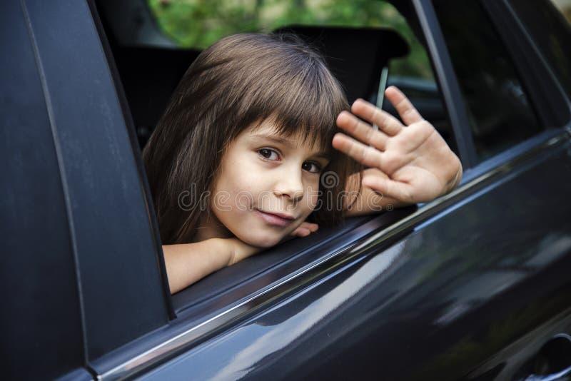 Niña que agita a través de la ventanilla del coche, adiós concepto foto de archivo libre de regalías