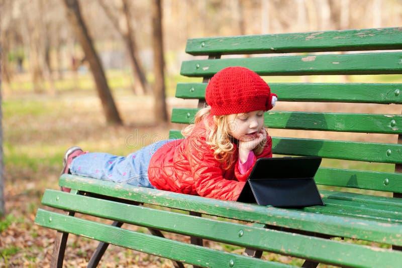 Niña que aprende con PC de la tableta en el parque. fotografía de archivo