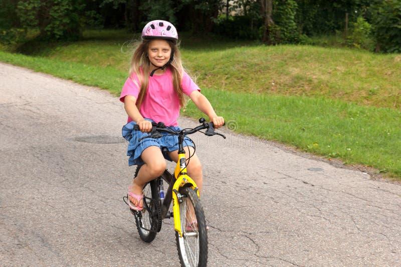Niña que aprende montar una bicicleta foto de archivo libre de regalías