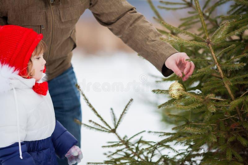 Niña que ayuda a su Navidad de adornamiento tres del padre al aire libre imagen de archivo libre de regalías