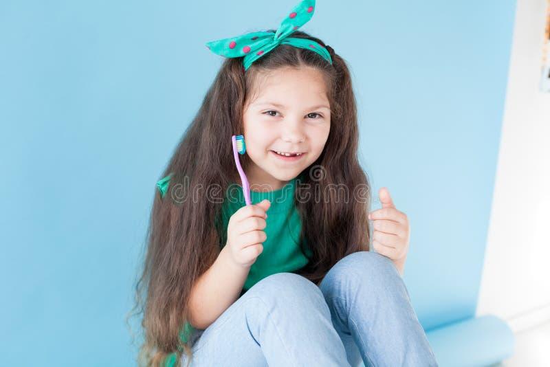 Niña que cepilla sus dientes con un diente de la odontología del cepillo de dientes imagen de archivo libre de regalías