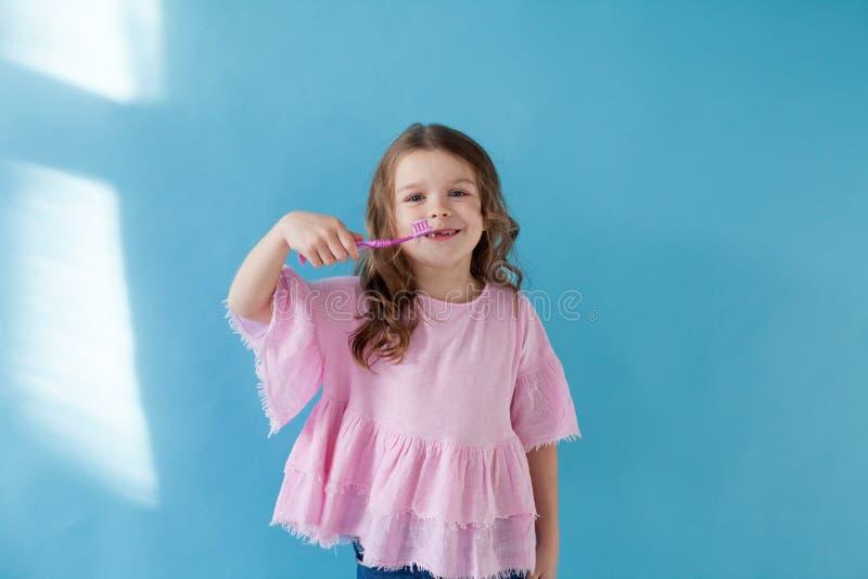 Niña que cepilla sus dientes con un diente de la odontología del cepillo de dientes imágenes de archivo libres de regalías