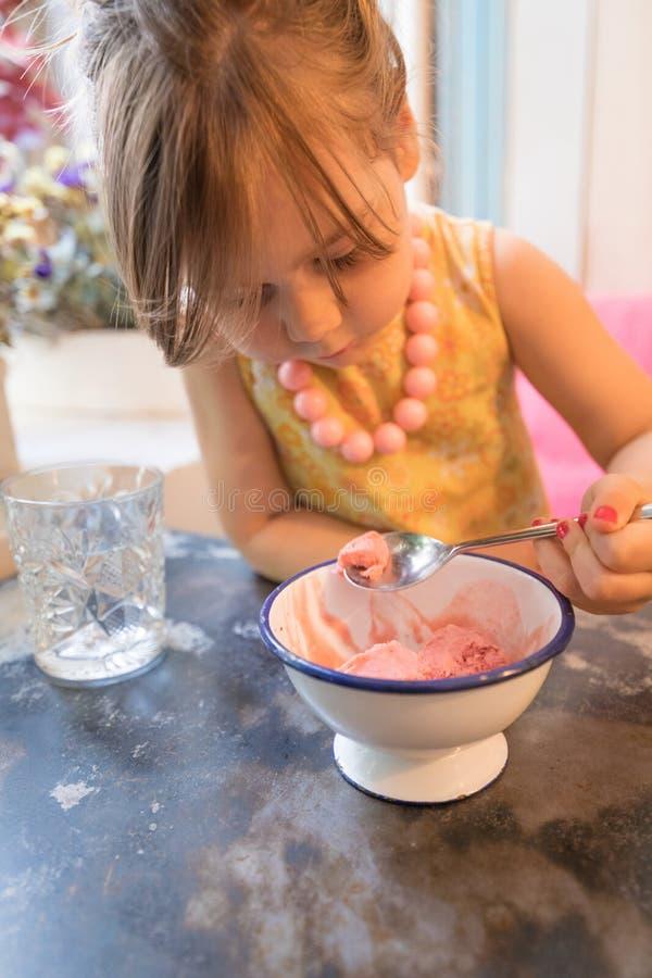 Niña que come el helado de fresa con la cuchara en restaurante imagen de archivo