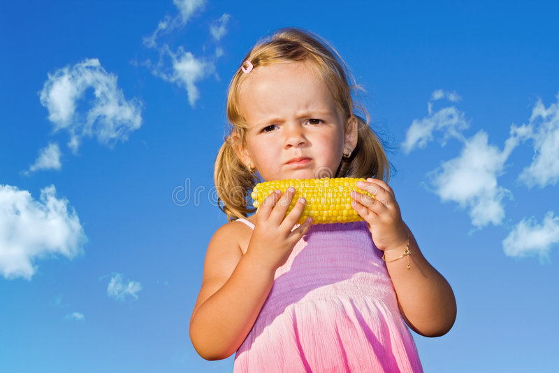 Niña que come el maíz dulce cocinado imagen de archivo