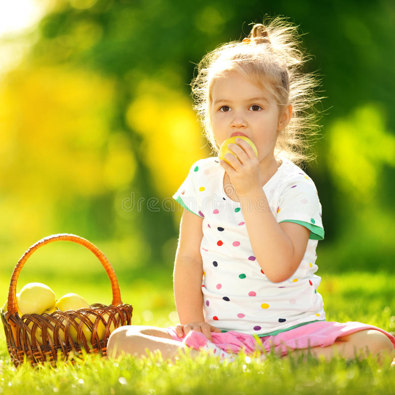 Niña que come la manzana en el parque fotografía de archivo libre de regalías