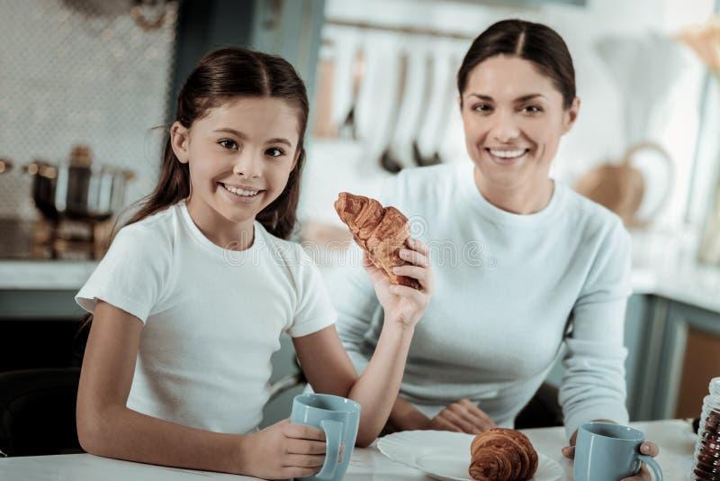 Niña que come los cruasanes en la cocina imagen de archivo