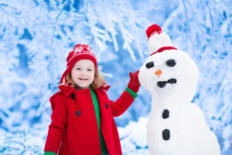 Niña que construye a un hombre de la nieve fotografía de archivo libre de regalías