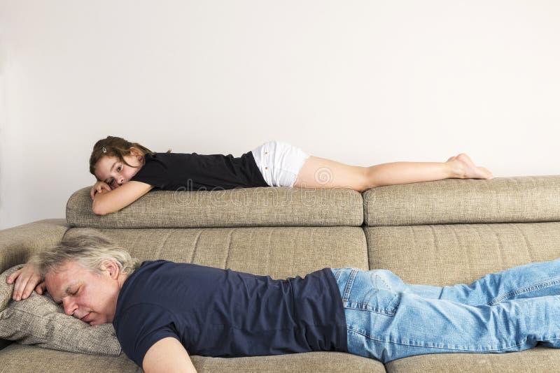 Niña que descansa con su papá en el sofá en casa imagenes de archivo