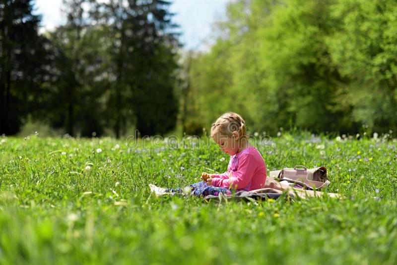 Niña que descansa sobre un prado verde entre las flores del prado imagenes de archivo